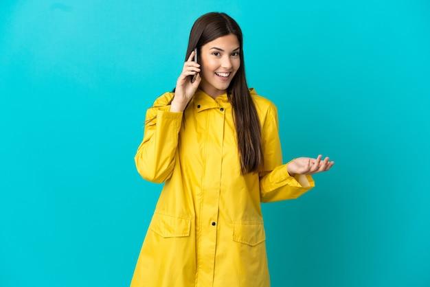 Brasileira adolescente vestindo um casaco à prova de chuva sobre um fundo azul isolado, conversando com alguém com o telefone celular