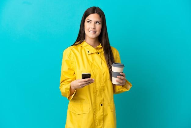 Brasileira adolescente vestindo um casaco à prova de chuva sobre um fundo azul isolado segurando um café para levar e um celular enquanto pensa em algo