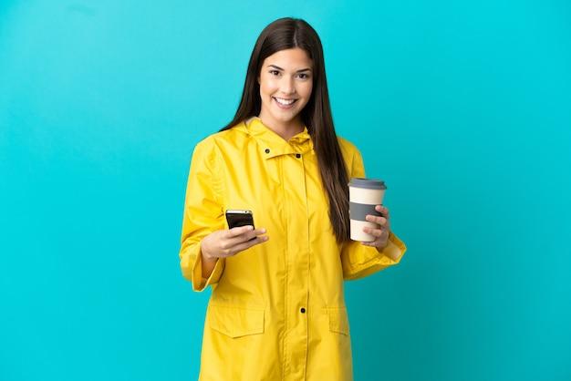 Brasileira adolescente vestindo um casaco à prova de chuva sobre uma parede azul isolada segurando um café para levar e um celular
