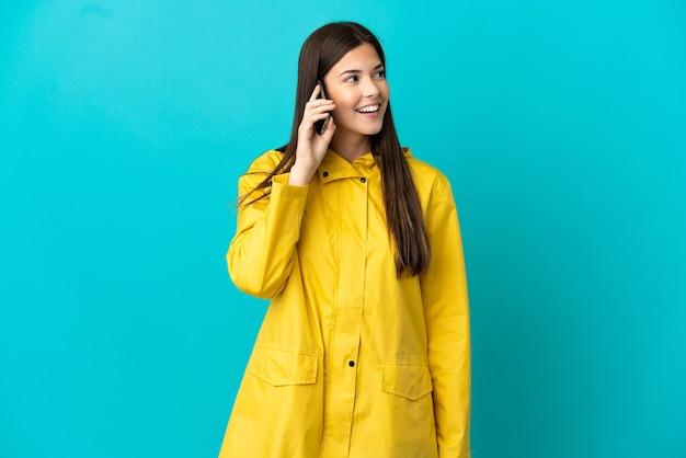 Brasileira adolescente vestindo um casaco impermeável sobre fundo azul isolado, conversando com o celular