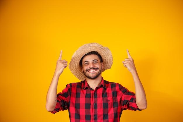 Brasileiro com roupas típicas da festa junina apontando para o lado