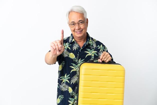 Brasileiro de meia-idade isolado em férias com mala de viagem e contando uma