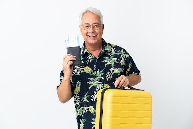 Brasileiro de meia-idade isolado em férias com mala e passaporte