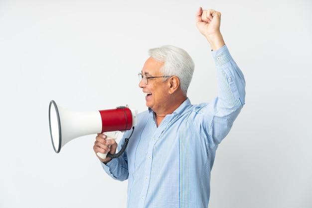 Brasileiro de meia-idade isolado em parede branca gritando em um megafone para anunciar algo em posição lateral
