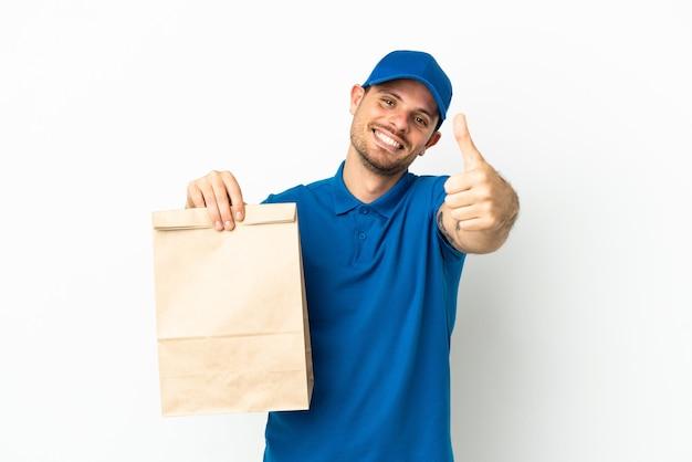 Brasileiro levando um saco de comida para viagem isolado no fundo branco com o polegar levantado porque algo bom aconteceu
