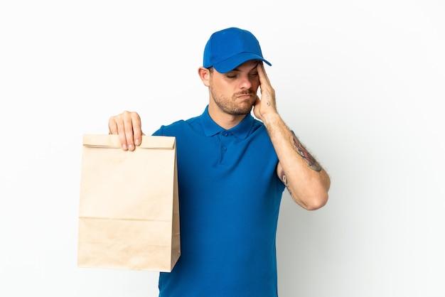 Brasileiro levando uma sacola de comida para viagem isolada no fundo branco com dor de cabeça