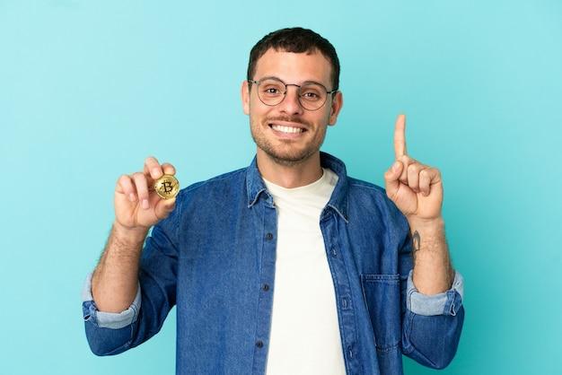 Brasileiro segurando um bitcoin sobre um fundo azul isolado apontando uma ótima ideia