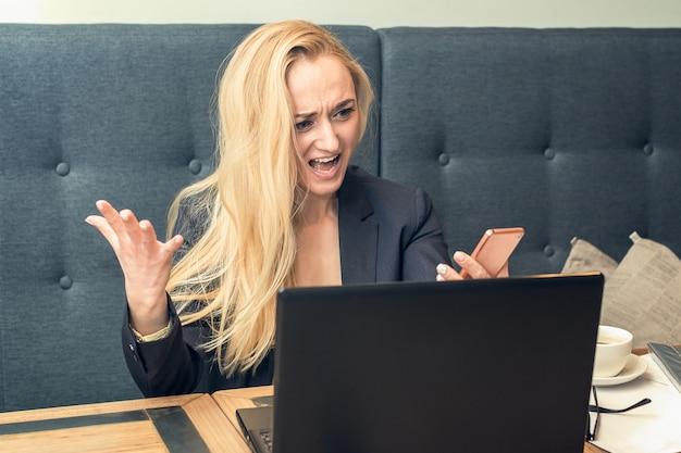 Brava jovem insatisfeita, olhando no smartphone telefone na frente do laptop.