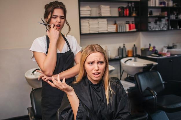Brava loira jovem cliente do sexo feminino gritando com cabeleireiro para um corte de cabelo feito mal