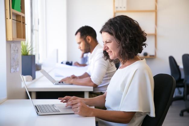 Brava mulher caucasiana, trabalhando com o laptop