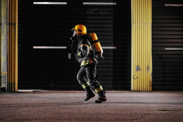 Bravo bombeiro em uniforme de proteção com equipamento completo correndo para cuidar do fogo