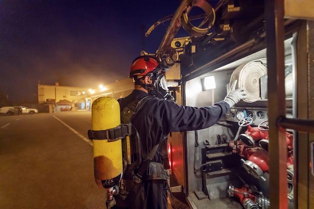 Bravo bombeiro tirando mangueira do caminhão de bombeiros para apagar o fogo à noite.