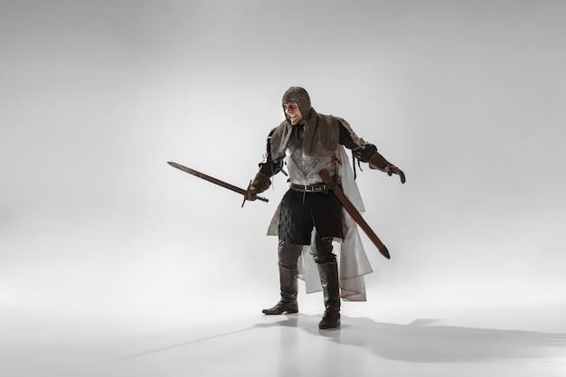 Bravo cavaleiro armado com arma profissional lutando isolado no fundo branco do estúdio. reconstrução histórica da luta nativa de guerreiros. conceito de história, hobby, arte militar antiga.