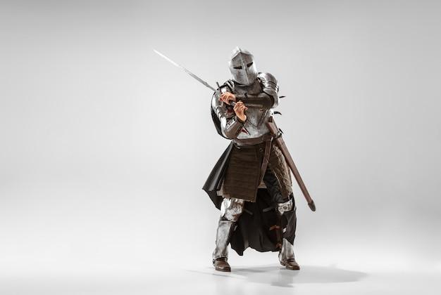 Bravo cavaleiro blindado com luta de arma profissional isolada no fundo branco do estúdio. reconstrução histórica da luta nativa de guerreiros. conceito de história, hobby, arte militar antiga.