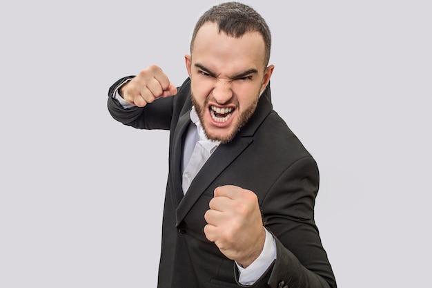 Bravo e rude jovem fica e mantém as mãos em punho. ele grita na câmera. o cara está pronto para lutar.