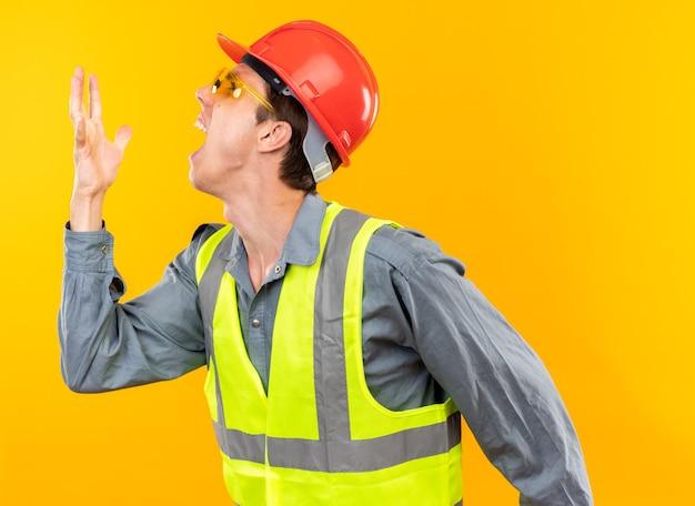 Bravo em pé na vista de perfil, jovem construtor de uniforme usando óculos, levantando a mão isolada na parede amarela