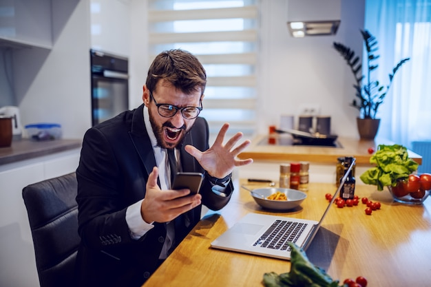 Bravo empresário caucasiano em terno sentado na cozinha em casa, segurando o telefone inteligente e gritando. à sua frente, na mesa, estão laptop, prato e legumes.