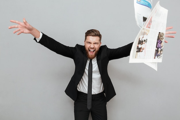 Bravo empresário louco no terno gritando e jogando jornal