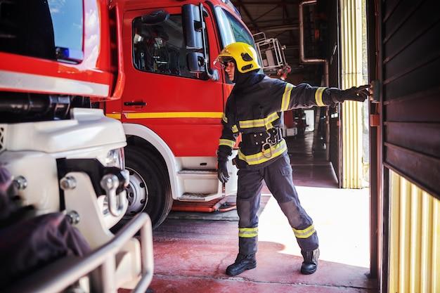 Bravo jovem bombeiro em uniforme de proteção com capacete na cabeça em pé no corpo de bombeiros e abrindo a porta