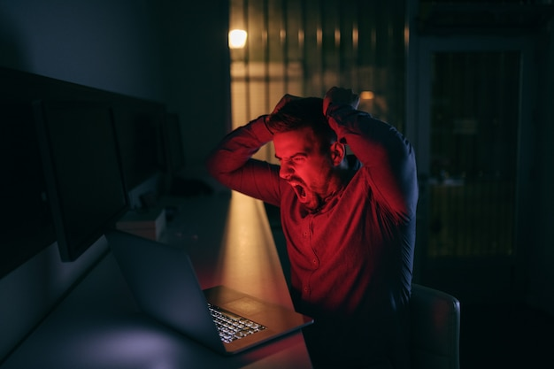 Bravo jovem caucasiano barbudo empregado olhando para laptop enquanto está sentado no escritório tarde da noite.