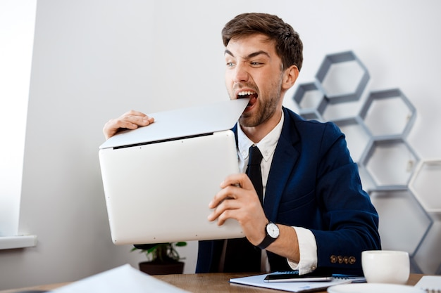 Bravo jovem empresário roendo laptop, fundo de escritório.