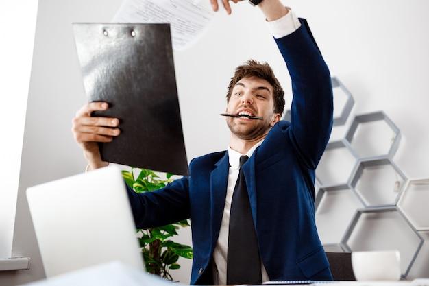 Bravo jovem empresário sentado no local de trabalho, plano de fundo do escritório.