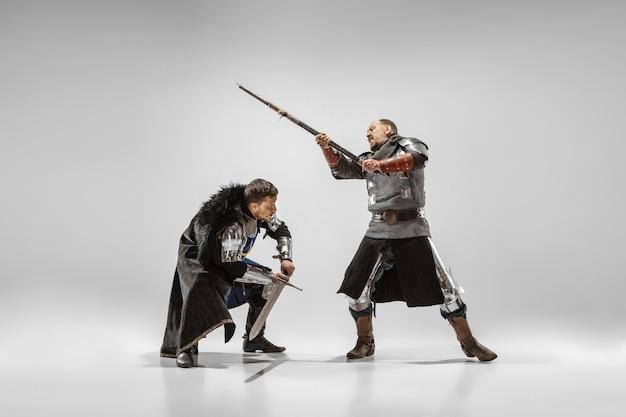 Bravos cavaleiros de armadura com armas profissionais lutando isolado no fundo branco do estúdio. reconstrução histórica da luta nativa de guerreiros. conceito de história, hobby, arte militar antiga.