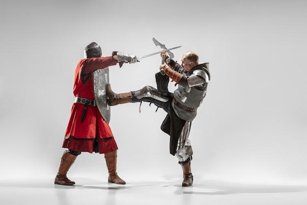 Bravos cavaleiros de armadura com armas profissionais lutando isolado no fundo branco do estúdio.