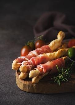 Breadsticks (grissini) com presunto, azeitonas e tomates - petiscos italianos tradicionais para vinho, foco seletivo, cópia espaço