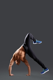 Breakdancer masculino sem camisa, mostrando alguns movimentos na copyspace cinza