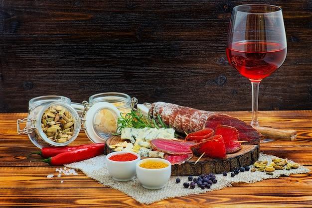 Bresaola curada fatiada com especiarias e um copo de vinho tinto no fundo rústico de madeira escuro.