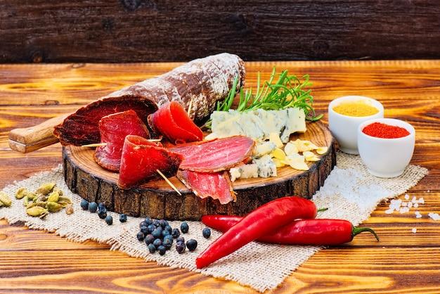 Bresaola curada fatiada com especiarias e um raminho de alecrim em fundo rústico de madeira escuro.