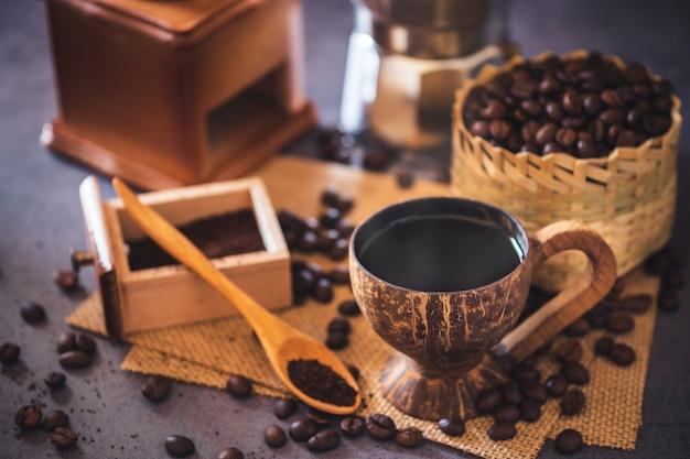 Brew café preto em copo de coco e iluminação da manhã. feijões de café roasted em uma cesta de bambu e em uma colher de madeira.