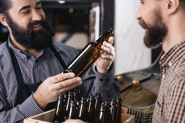 Brewer testa garrafas para o trabalho de amor de enchimento de cerveja.