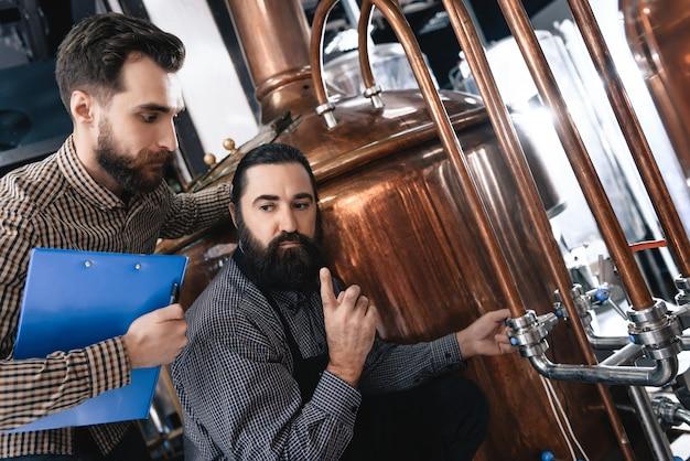 Brewers ansiosos verificam equipamentos e tubulações.