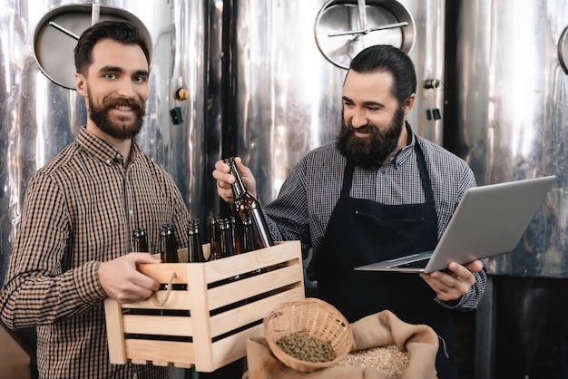 Brewers felizes que inspecionam garrafas de cerveja na fábrica.