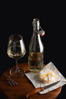 Brie de queijo e vinho branco servidos na placa de madeira marrom sobre fundo preto.