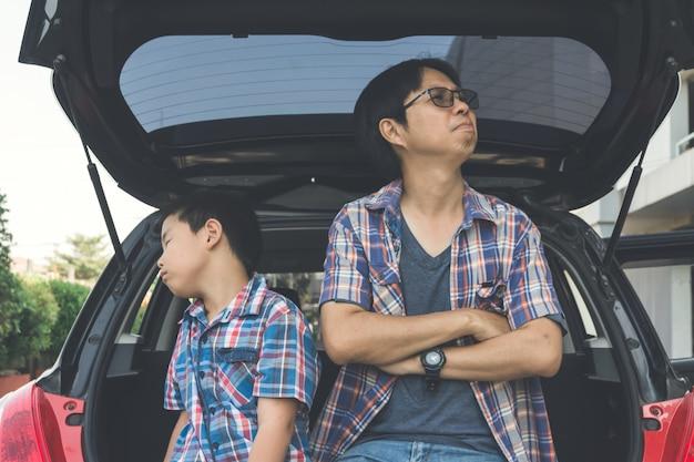 Briga de filho pequeno e pai sentado no tronco do carro