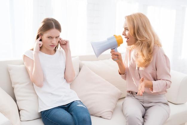 Briga entre mãe e filha no quarto branco.