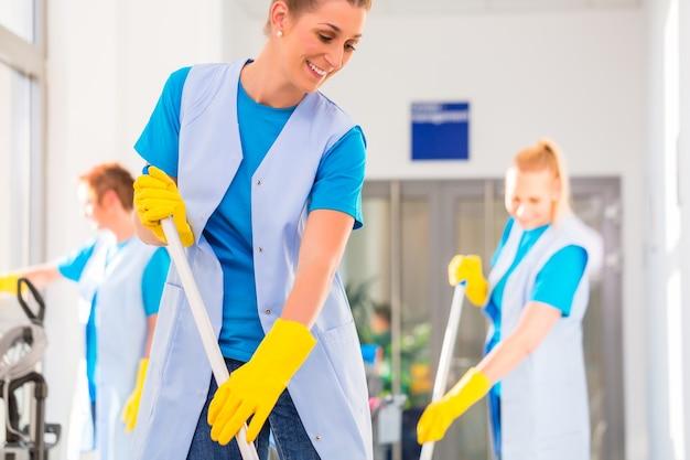 Brigada de limpeza comercial trabalhando esfregando o chão