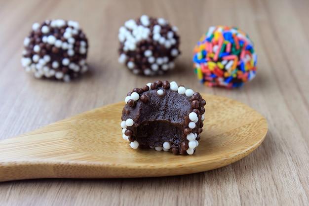 Brigadeiro (brigadeiro), chocolate doce típico da culinária brasileira coberto com partículas, em um fundo de madeira