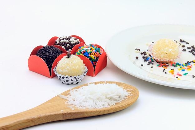 Brigadeiro (brigadeiro), doce de chocolate típico da culinária brasileira coberto com partículas, em fundo branco