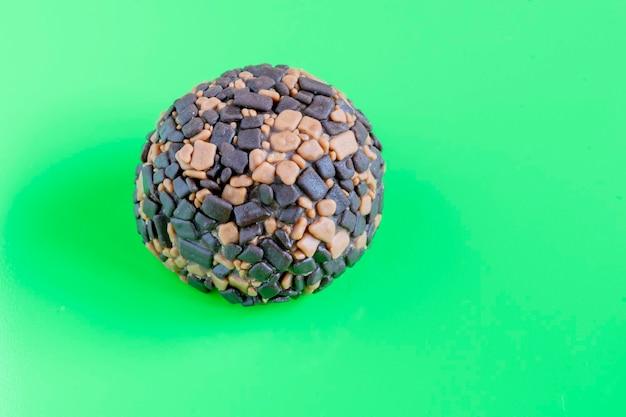 Brigadeiro. leite doce condenado com chocolate e café, com fundo verde.