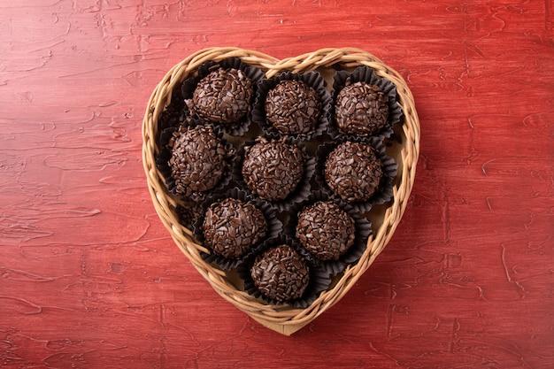 Brigadeiro.tradicional chocolate doce brasileiro em cesta em forma de coração.