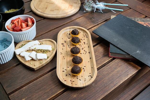 Brigadeiros alinharam-se ao lado do pistache turron em uma mesa de madeira. ao lado de creme de manteiga, morangos, pistache, pirulito de chocolate e um livro.