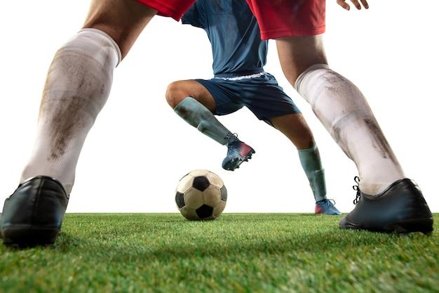 Brigando. feche as pernas do futebol profissional, jogadores de futebol lutando pela bola em campo isolado na parede branca. conceito de ação, movimento, emoção de alta tensão durante o jogo. imagem recortada.