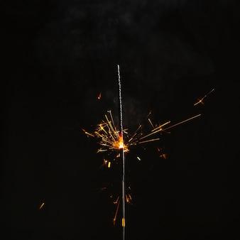 Bright sparkler on dark background