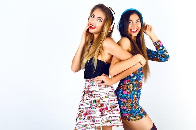 Brigit fashion portrait de duas melhores amigas dj girls, usando vestidos de festa sensuais, fones de ouvido e ouvindo suas músicas favoritas.
