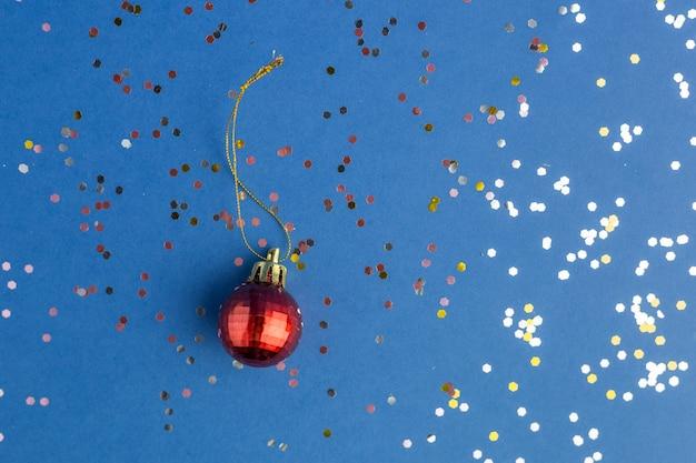 Brilha com bugiganga vermelha sobre fundo azul moderno. cenário festivo para projetos. estilo liso leigo. vista do topo. cor do ano.