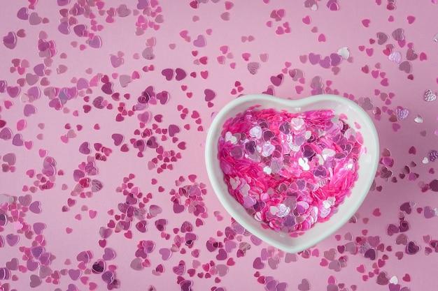 Brilha na tigela em forma de coração, copo cerâmico na mesa-de-rosa com brilhos. decoração de dia dos namorados com corações. copie o espaço, plana leigos.